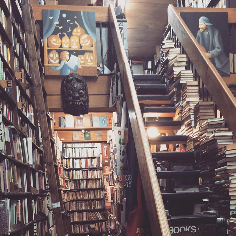 a cozy used book store with books from floor to ceiling and piled along one side of the stairs