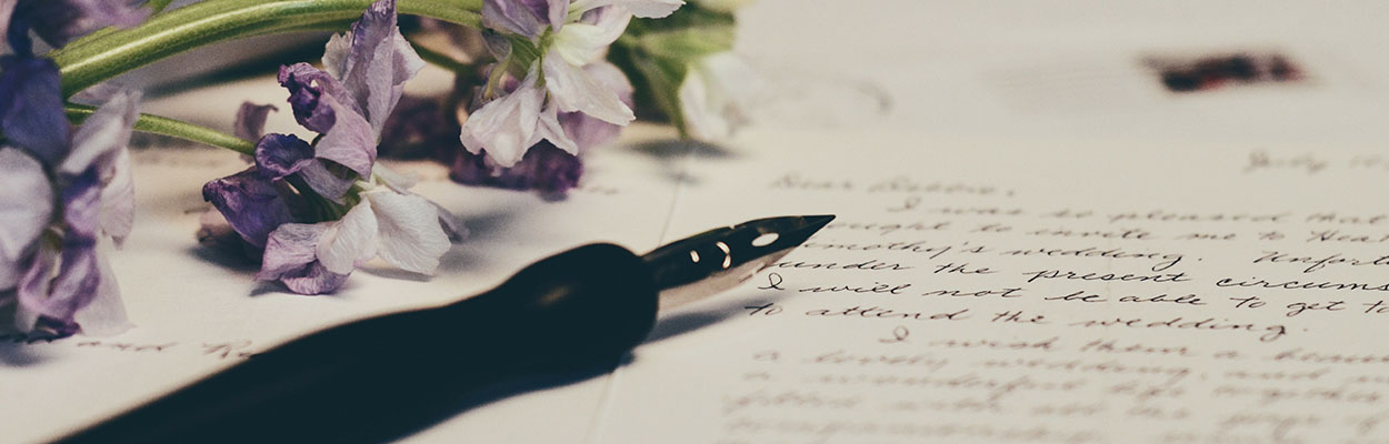a pen and purple flowers atop a sheet of paper with cursive writing