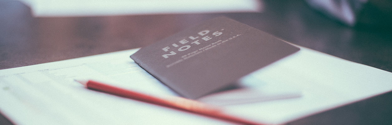 A notebook with the words Field Notes on the cover and a red pencil