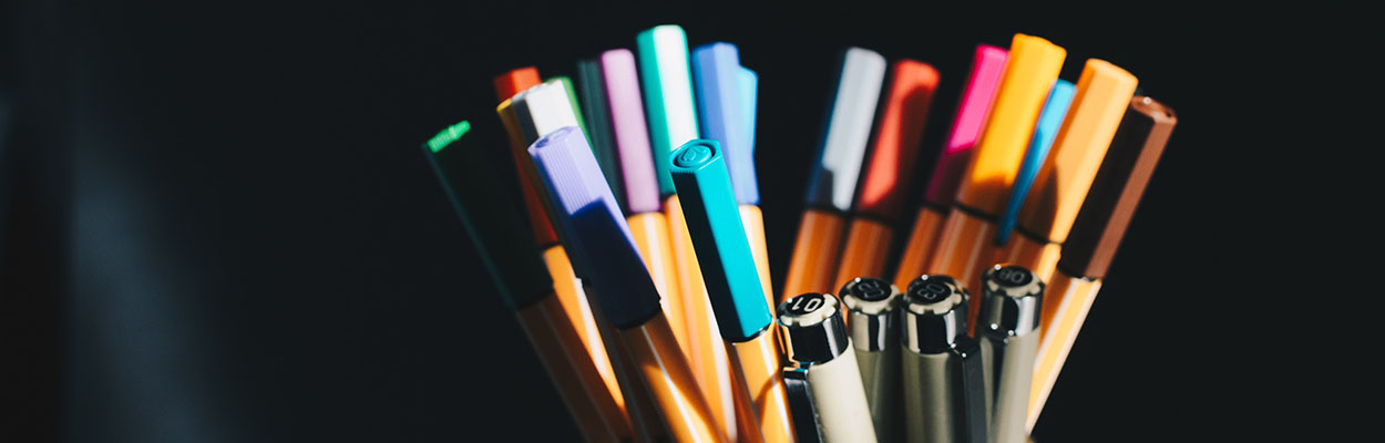 colorful pens against a black background