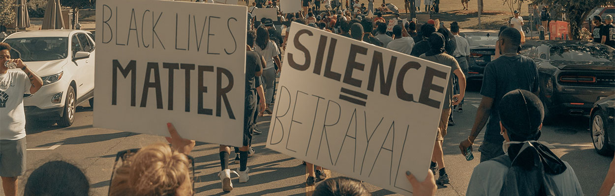 Image of a BLM protest with signs saying Black Lives Matter and Silence = Betrayal
