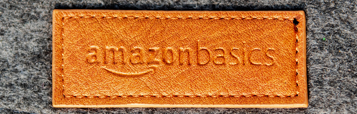 a faux leather patch bearing the amazon basics logo on a grey felt background